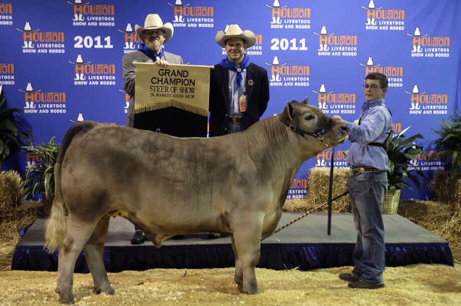 Paul Somerville, left, and Tilman Fertitta bid $350,000 to win the 2011 Grand Champion Junior Market Steer shown by Koby Long, right. Photo: Cody Duty, Chronicle