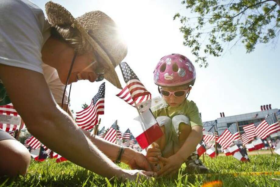 Sara Rutledge helps her son Ian, 4, place flags on Saturday at Discovery Green to honor Texas-born troops killed in recent wars. Each flag contained details about the fallen Texan. Photo: Michael Paulsen, Chronicle