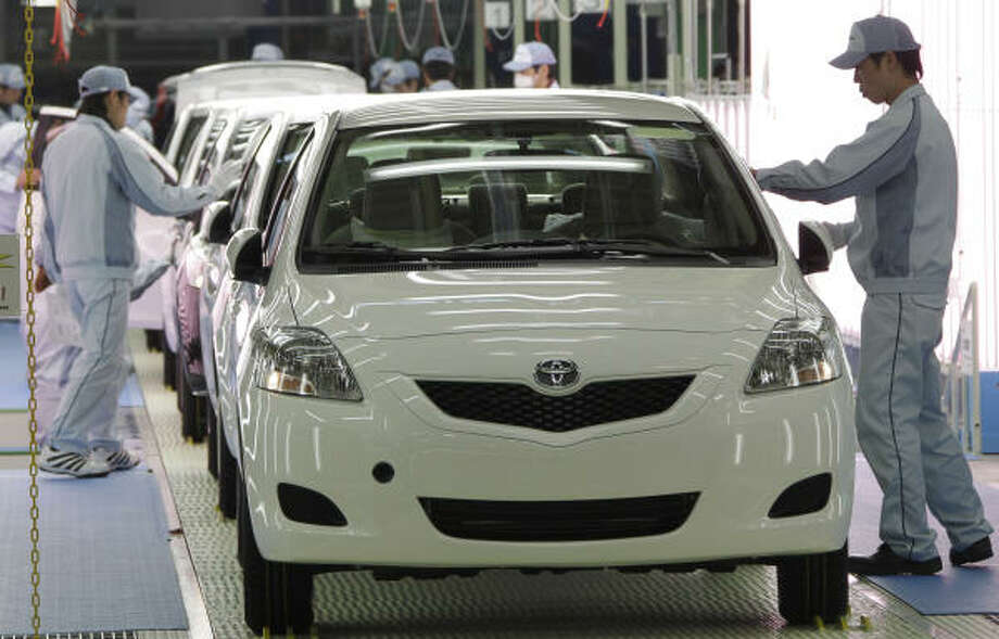 Workers last month gave the final check on Yaris compact sedans, set for export to North America, on a newly opened Toyota assembly line in Japan. Photo: Koji Sasahara:, AP