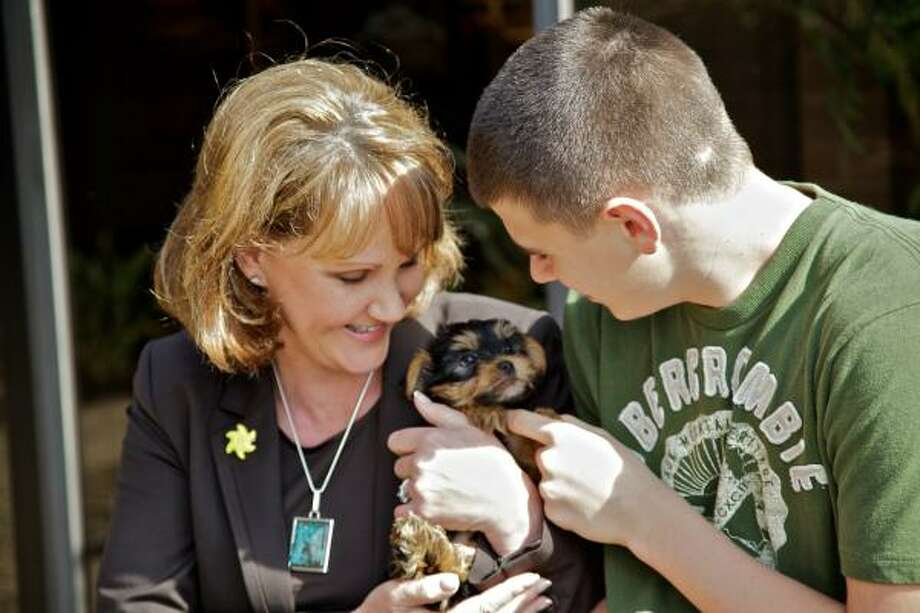 "Fourteen year old cancer survivor and ""Sunshine Kid"" Cory Filer and branch manager Debra Blenderman enjoy the morning with Hope, an eight week old Yorkie that will be auctioned at the Sunshine Kids fundraising event being sponsored by the Bay Area Prudential Gary Greene Realtors. Photo by Maria-Patricia Cortez. Photo: Maria-Patricia Cortez, For The Chronicle"
