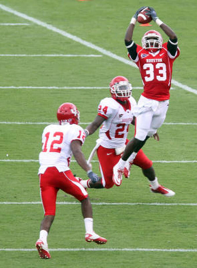The UH Red team's Marcus Williams pulls in a pass over the White team's Chevy Bennett, left, and Kent Brooks. Photo: James Nielsen, Chronicle