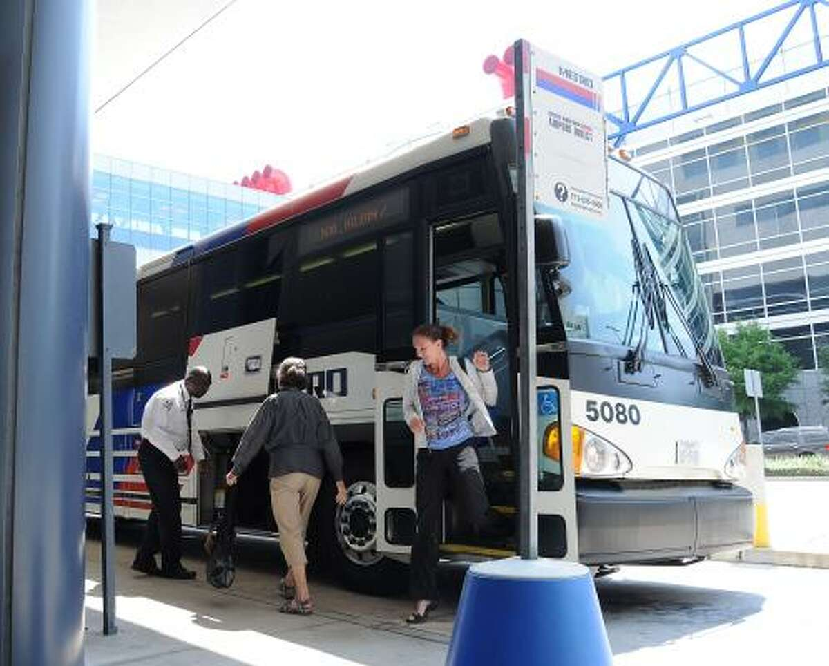 Passengers unload from Metro's Airport Direct bus service outside the Hilton Americas Hotel downtown.