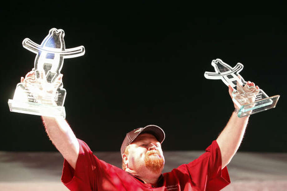 Craig Sharry, with Texas Pepper Jelly, holds up his awards after being named 2011 Grand Champion Saturday at the World's Championship BBQ Contest. He won first overall in the brisket category and the overall champion award. Photo: Todd Spoth, Chronicle