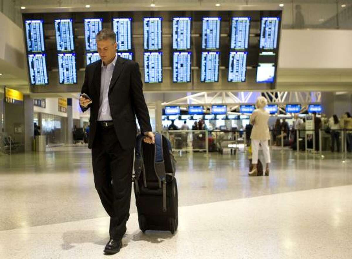 Steve Loden makes his way through Terminal C at Bush Intercontinental Airport to catch his flight. Loden is a frequent flier for business, but when he saw the fare for a trip to a family reunion in Indiananpolis this summer, he balked and is driving instead.