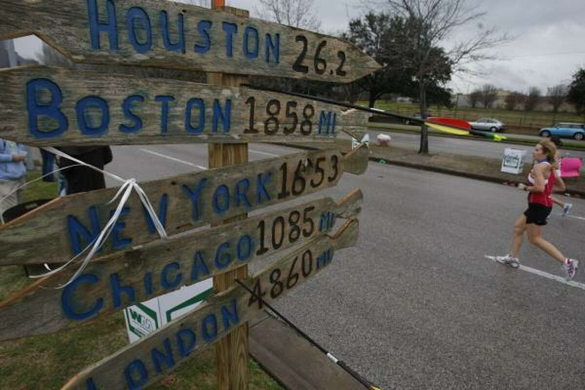 A sign near the Houston Hash House Harriers beer stop on the 24th mile of the course along Allen Parkway reminds runners of how close they are to several major marathons.