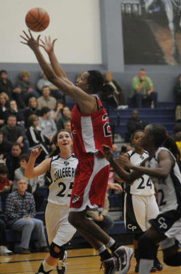 Atascocita senior post Rachel Mitchell, center, skies for a rebound on Friday night. Photo: Jerry Baker, For The Chronicle