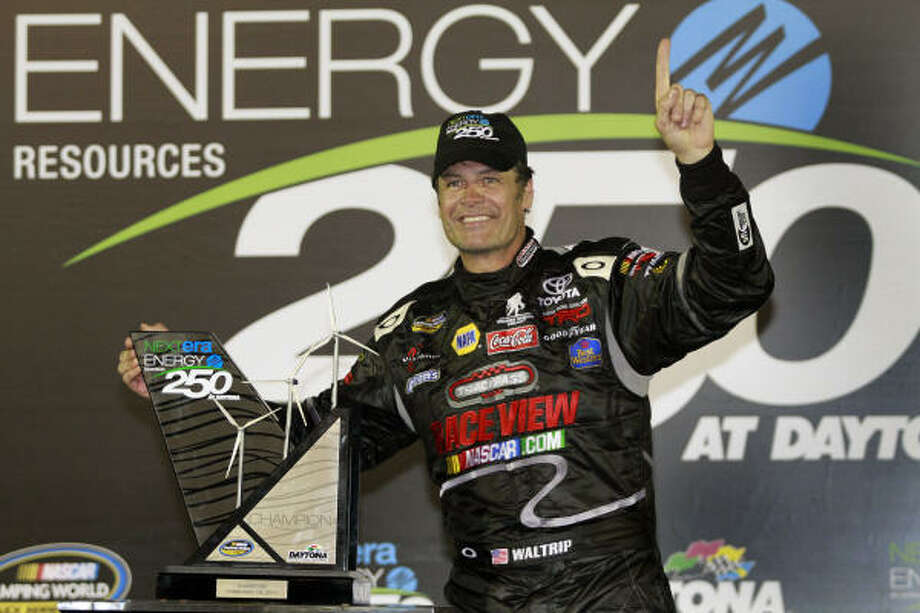 Michael Waltrip stands next to the trophy as he celebrates in Victory Lane after winning the NextEra Energy Resources 250 auto race at the Daytona International Speedway on Friday night. Photo: Terry Renna, AP