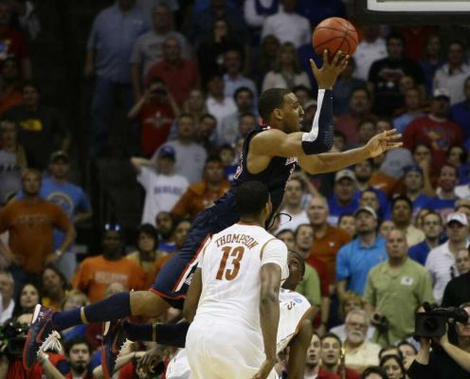 Arizona forward Derrick Williams makes an acrabatic play to tie the score as Texas guard Jordan Hamilton tries to draw a charge in the final minute on Sunday. Photo: Nick De La Torre, Chronicle