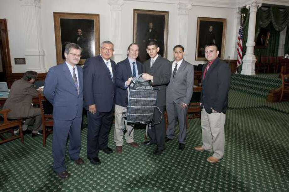 COURTESY PHOTO THE GIFT OF A SOLAR BACKPACK: Three seniors from DeVry University in Houston presented Kevin Good, director of Texas Parks & Wildlife, with a solar backpack, the first of its kind, on Feb. 28 at the Texas State Capitol. The students applied their knowledge and skill sets to create the backpack, which can be used to power critical items for wilderness survival, such as distress signal lights, heaters, cell phones, walkie-talkies and radios. At the presentation, were Teddy Ivanitzki, associate dean, DeVry University, left; state Sen. Mario Gallegos Jr., D-Houston, District 6; Good and students William Campoverde, Luis Soriano and Jimmy Espinoza. Photo: ALL
