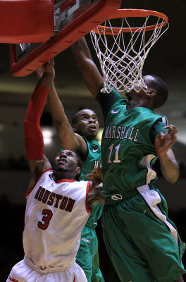 UH forward Maurice McNeil is able to sneak the ball past Marshall forward Tirrell Baines, back, and Nigel Spikes (11) for a layup in the first half on Tuesday night. Photo: Nick De La Torre, Chronicle