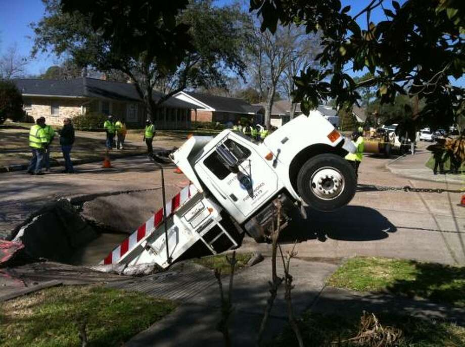 A city of Houston dump truck fell into a giant sinkhole Tuesday morning in southwest Houston. Photo: Karen Warren, Chronicle