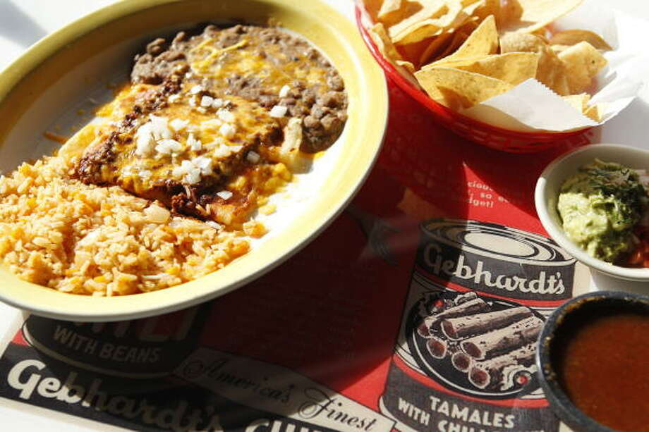 """Cheese enchiladas with chili con carne on a table decorated with an old Gebhardt's advertising at El Real Tex-Mex Cafe, 1201 Westheimer,  shown Wednesday, Feb. 23, 2011, in Houston.  Chef Bryan Caswell and partners, Bill Floyd and Robb Walsh, are calling the restaurant  """"vintage Tex-Mex"""".   ( Melissa Phillip / Houston Chronicle ) Photo: Melissa Phillip Photos :, Chronicle"""