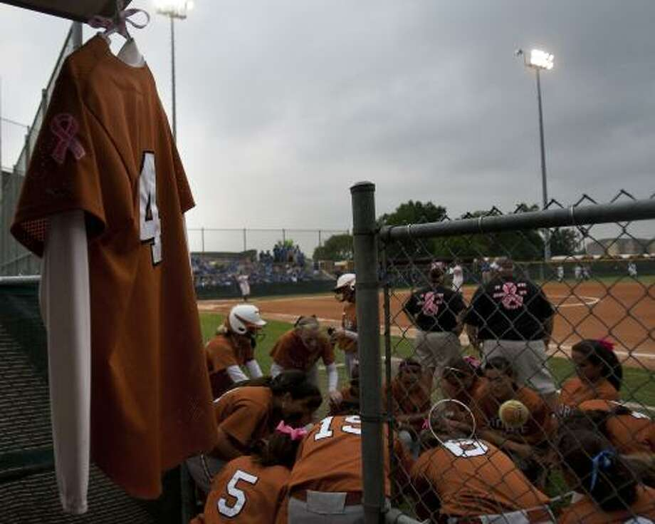 NOT FORGOTTEN: The jersey belonging to former Lady Longhorns softball player Gabby Romero, a teammate who died of cancer in 2009, hangs in the dugout as the Dobie High School softball team prays before a match. The team took Romero's jersey to every game, and cheered her name in every pre-game huddle. Photo: Cody Duty, Houston Chronicle