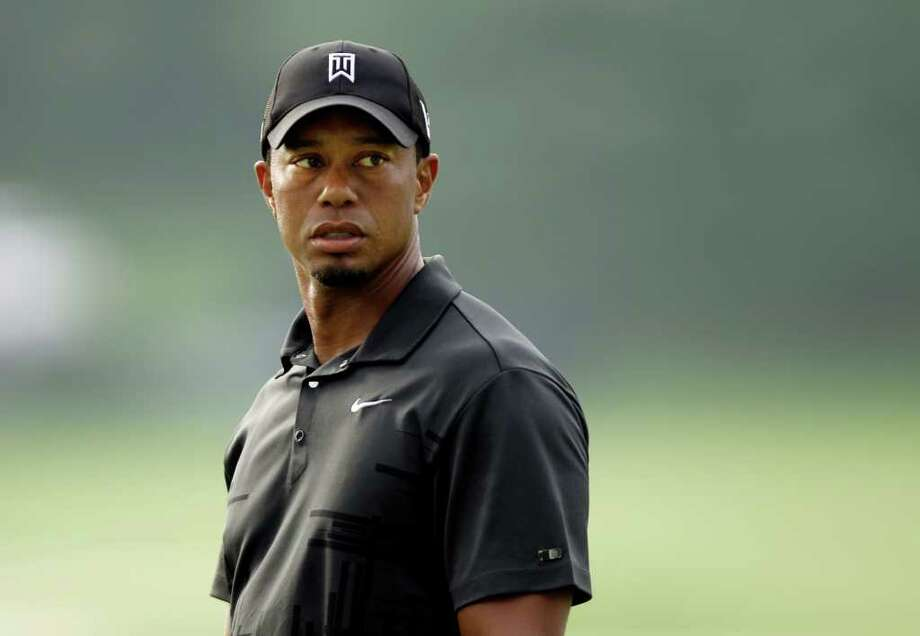 Tiger Woods watches his putt on the ninth green during practice for the Bridgestone Invitational golf tournament at Firestone Country Club in Akron, Ohio Tuesday, Aug. 2, 2011. (AP Photo/Mark Duncan) Photo: Mark Duncan, STF / AP