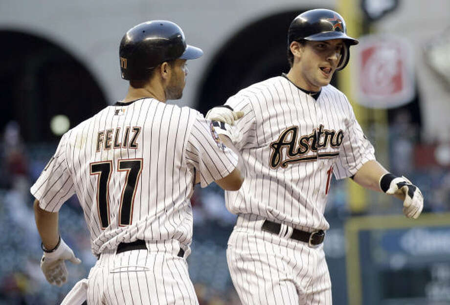 The Astros' Tommy Manzella, right, is congratulated by teammate Pedro Feliz after both scored on Manzella's home run during the second inning. Photo: David J. Phillip, AP