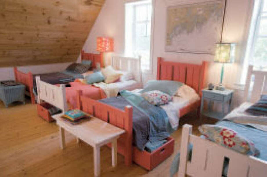 Summer hospitality: In this setting, beds are arranged with little regard for placement of windows, and that is fine because it extends the service of the space. The goal was to fit as many kids as possible into the attic room.