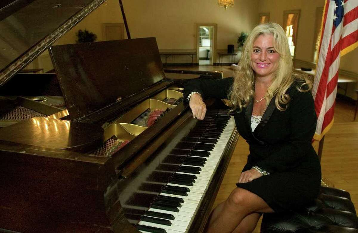Catherine Urso, also known by her stage name as Katerina Tea, poses in the Alexandria Room at Edmond Town Hall in Newtown on Tuesday, Aug. 2, 2011. Urso's business, Magical Music for Humanity, does original composition and performances for fundraisers to help others.