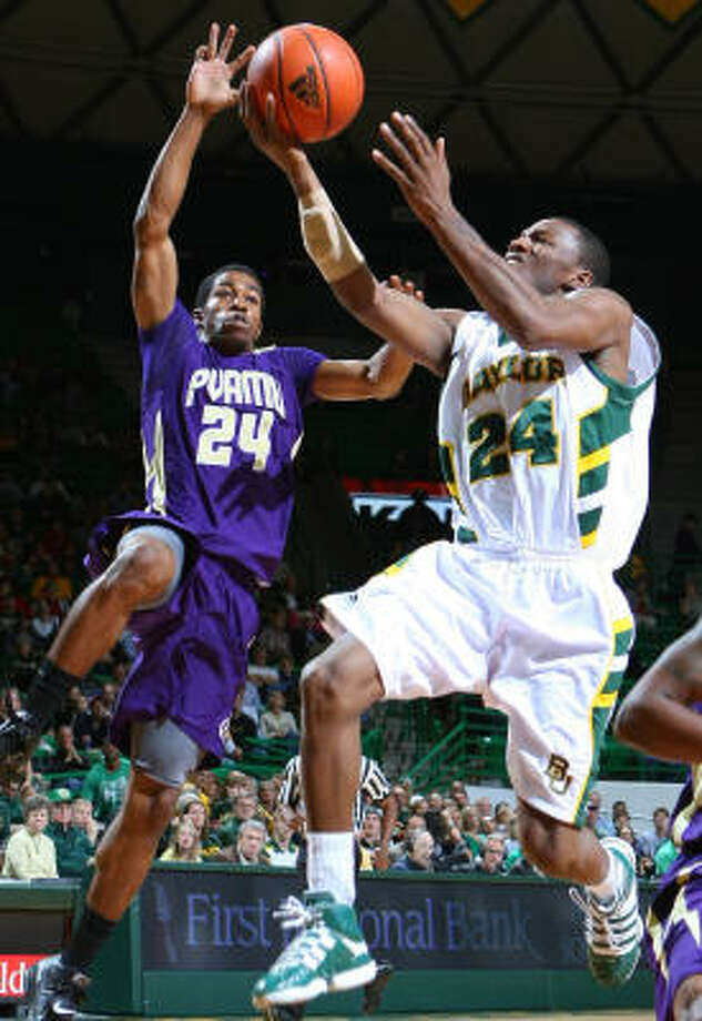 Baylor guard LaceDarius Dunn, right, scores against Prairie View A&M guard Duwan Kornegay, left, in first half on Monday night. Photo: Jerry Larson, AP