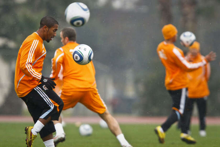The Dynamo's Corey Ashe, left, gets his touches during warmup drills for the first practice of the season. Photo: Michael Paulsen, Chronicle