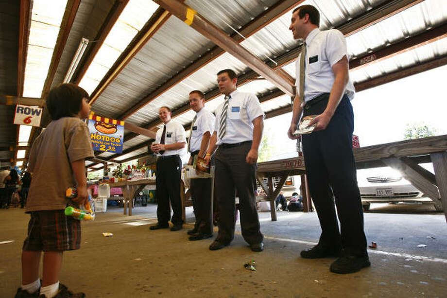 Elders Aaron Porter, from left, Sean Herrmann, Wayland McGary and Aaron Allbee talk with a boy about the Mormon faith during a weekly visit to a flea market popular with Hispanics in north Houston. Photo: Michael Paulsen, Chronicle