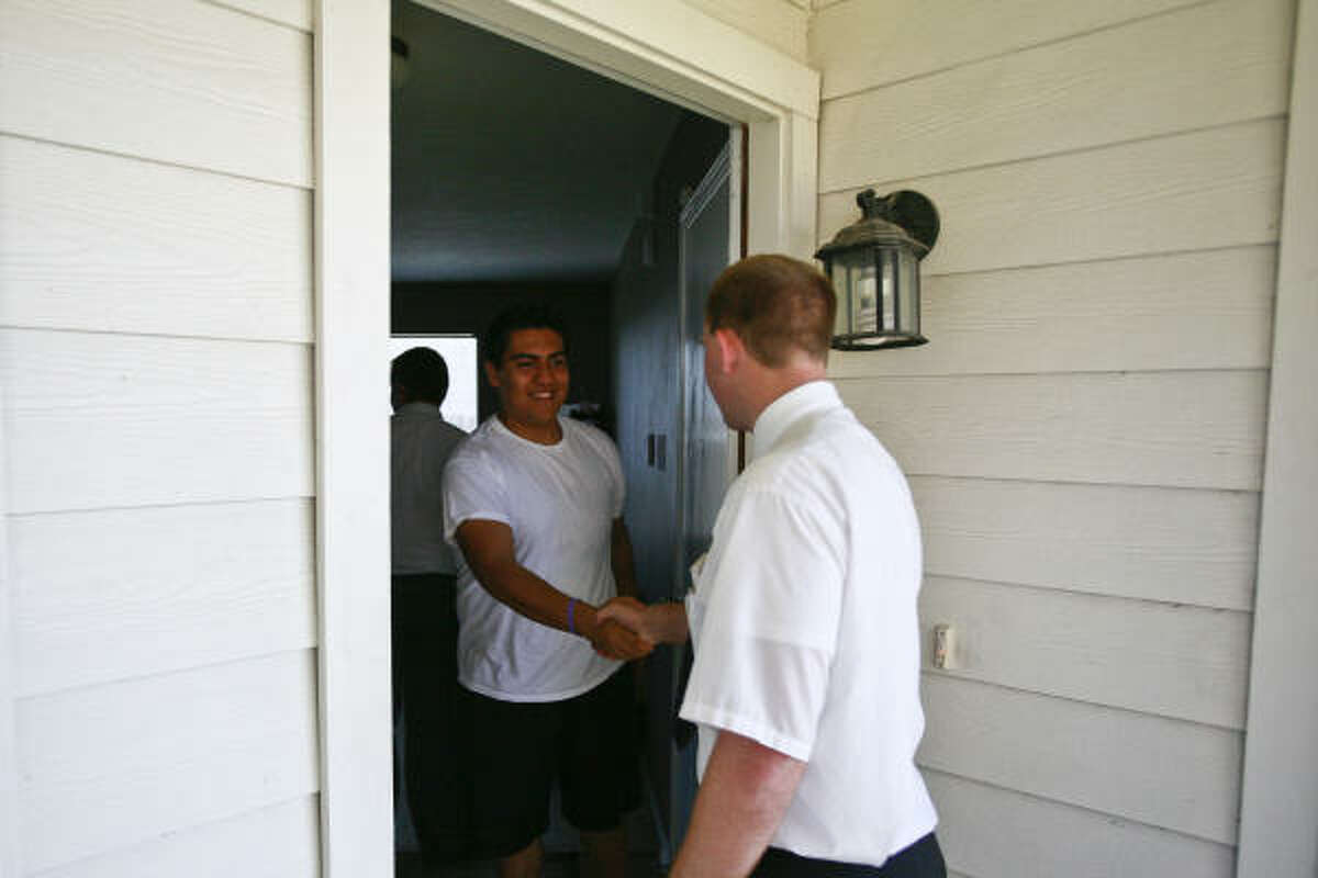 Agustin Alcantara greets Aaron Porter at his family's home during a teaching appointment.