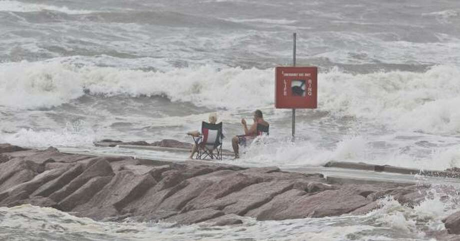 A couple with folding chairs take in Tropical Storm Hermine's wave action Tuesday at 37th Street and Seawall Boulevard in Galveston. Photo: James Nielsen, Chronicle