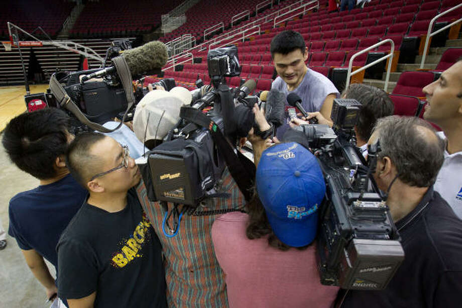 Rockets center Yao Ming attracts a crowd of media members after practice at the Toyota Center on  Saturday. Photo: Smiley N. Pool, Houston Chronicle