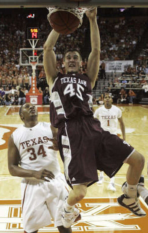 Texas A&M forward Nathan Walkup dunks in front of Texas center Dexter Pittman. Photo: Harry Cabluck, AP