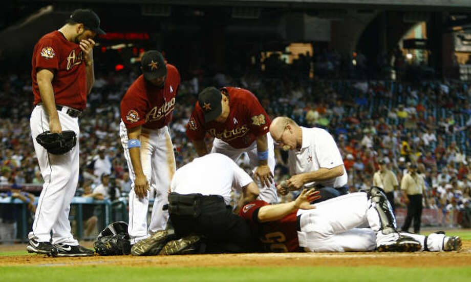 Astros' athletic trainers Rex Jones and Nathan Lucero work on catcher Humberto Quintero. Photo: Karen Warren, Chronicle