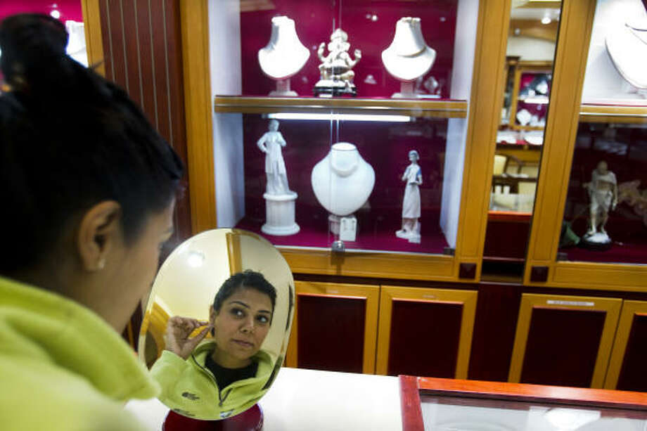 Tanya Gorowara looks in a mirror at an earring as she shops Wednesday at jewelry story Karat 22 in Houston. Aku Patel, owner of Karat 22, said gold prices are the highest he has seen and that shoppers are purchasing fewer traditional Diwali gifts. Photo: Brett Coomer, Chronicle