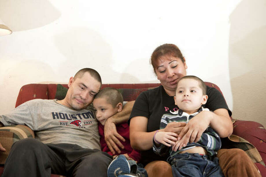 From left, Juan Carlos Tobias, Christopher Tobias Diaz, 6; Patricia Diaz, and Christian Tobias Diaz, 4, have a happy home in Pasadena despite economic drawbacks. Photo: Todd Spoth, Chronicle