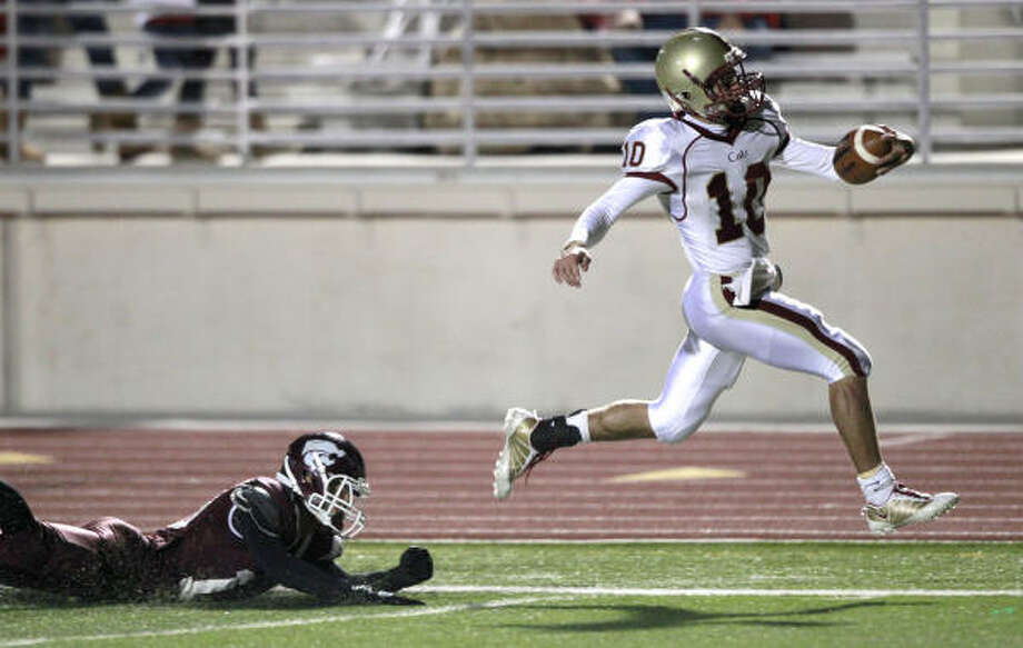 Cy Woods quarterback Colton Huntsman leaps past Clear Creek safety Logan Jentzen for a 47-yard touchdown run during the first half on Saturday night. Photo: Brett Coomer, Chronicle