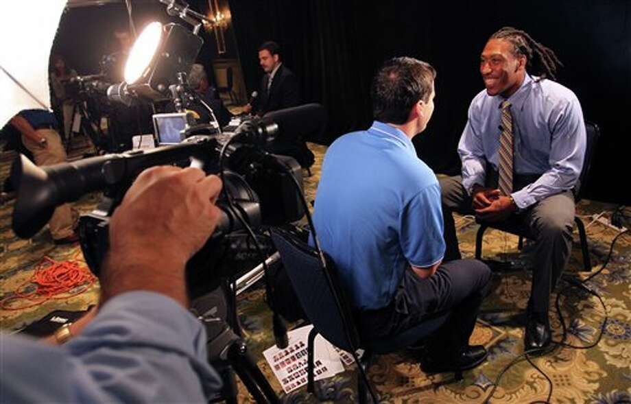 West Virginia defensive end Bruce Irvin, right, answers questions during a television interview at the Big East football media day Tuesday, Aug. 2, 2011, in Newport, R.I.. (AP Photo/Stew Milne) Photo: AP
