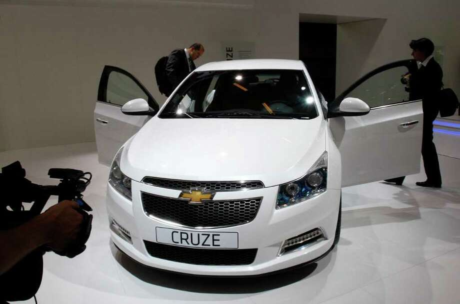 FILE - In this Oct. 1, 2010 file photo, visitors inspect the new 2011 Chevrolet Cruze Hatchback during a press day of the Paris Auto Show. General Motors said Tuesday, Aug. 2, 2011, its U.S. sales rose nearly 8 percent last month, led by fuel-efficient vehicles such as the Chevrolet Cruze car. (AP Photo/Michel Euler, File) Photo: Michel Euler, STF / AP2010
