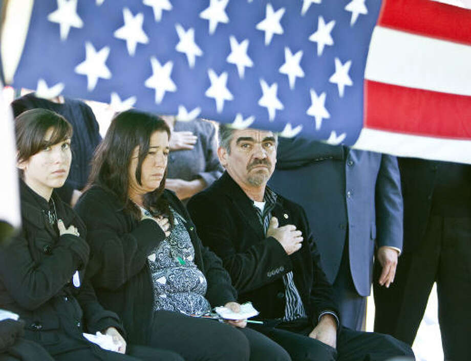 Army Spc. Pedro Maldonado's twin sister Bianca Maldonado, left, father Pedro Maldonado, right, and his wife, Maria Maldonado, center, watch as the honor guard folds the flag which was draped over the soldier's casket Monday at San Jacinto Cemetery. Photo: James Nielsen, Houston Chronicle