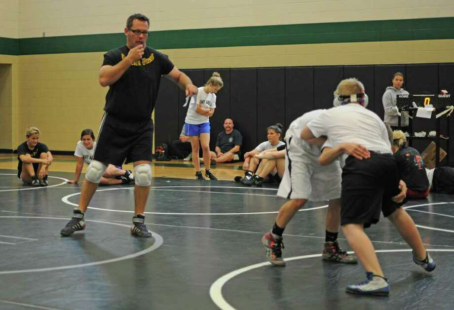 Clear Lake High School wrestling coach Brian Palazzi, left, referees a match during the 2011 Clear Creek ISD Bay Area Summer Wrestling Camp in June at Clear Falls High School in League City. The sport continues to grow in the area. Photo: L. Scott Hainline / freelance