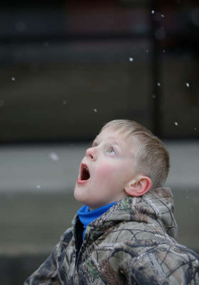 Garrett Baumgartner, 8, of The Woodlands tries to catch a few flakes Tuesday while his sisters were at a dance lesson in Magnolia. Photo: Melissa Phillip, Chronicle