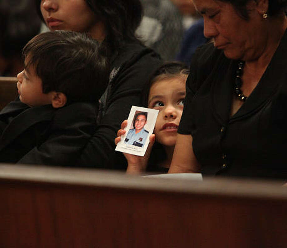 A family member holds a photo of Houston Police Officer Eydelmen Mani, whose funeral was held Saturday at Saint Charles Borromeo Catholic Church. Photo: Mayra Beltran, Chronicle