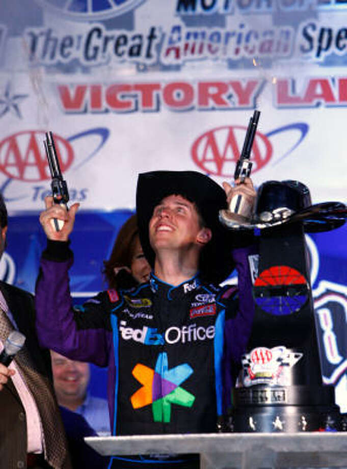 Denny Hamlin fires the winner's commemorative six-shooters in victory lane after winning the Texas 500 at Texas Motor Speedway on Sunday in Fort Worth. Photo: David Kent, MCT