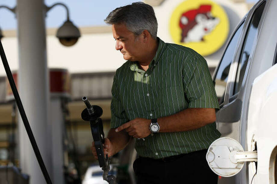 Gordon Spradley of Houston gases up this week at the Buc-ee's in Luling on Interstate 10. Gasoline price forecasters say more decreases are likely coming in the weeks ahead. Photo: Jerry Lara :, San Antonio Express-News