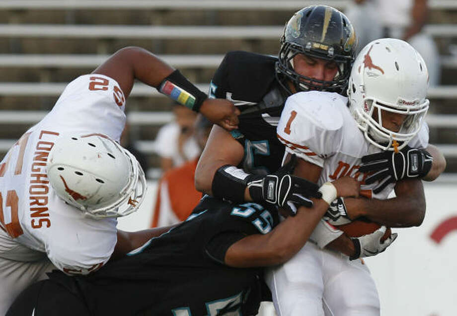 Dobie's Demarcus Boyd tries to break the tackles by two Pasadena Memorial defenders. Photo: Melissa Phillip, Chronicle