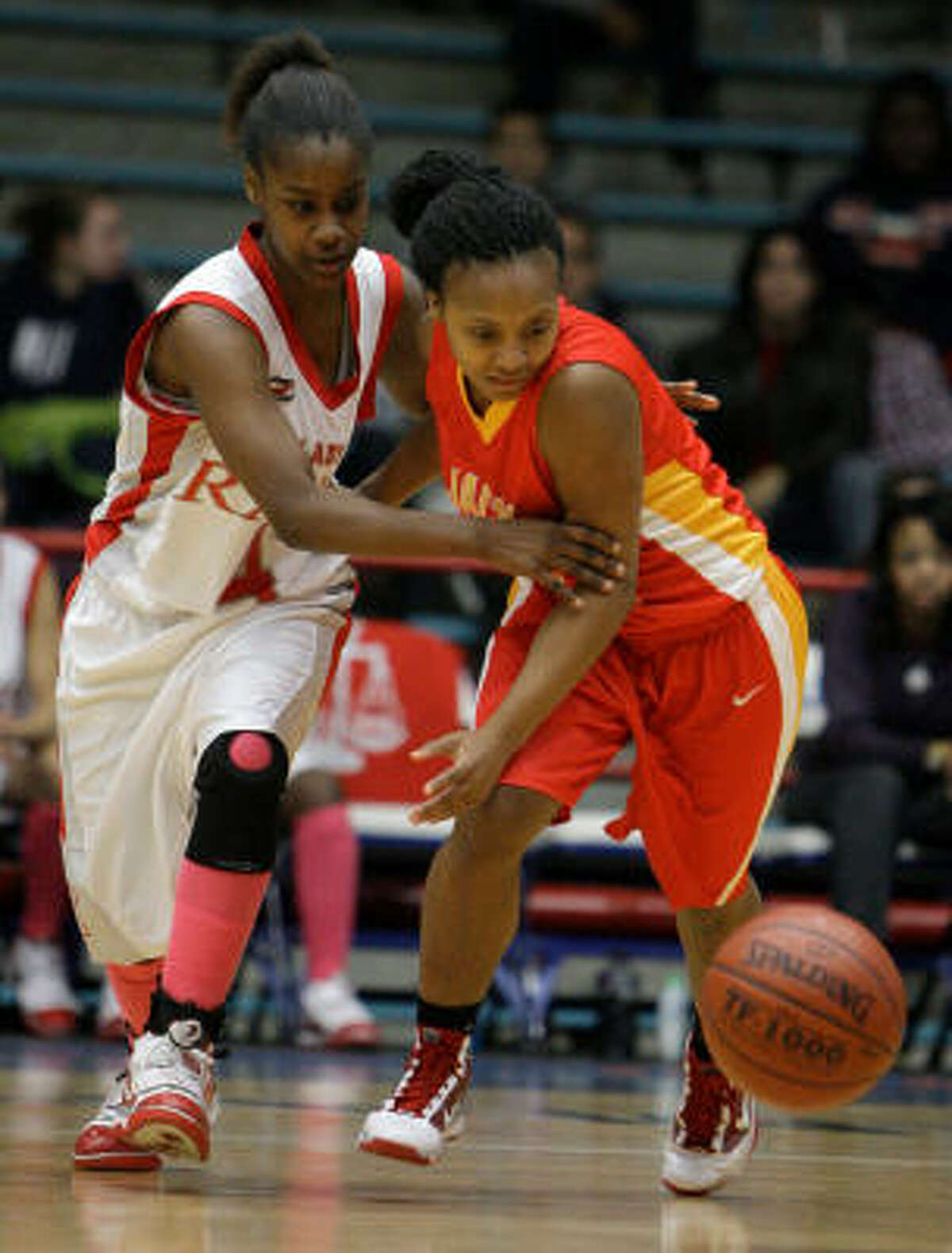 Waltrip's Chelsa Singer, left, and Yates' Jaeisha Johnson tangle as they go go for the ball.