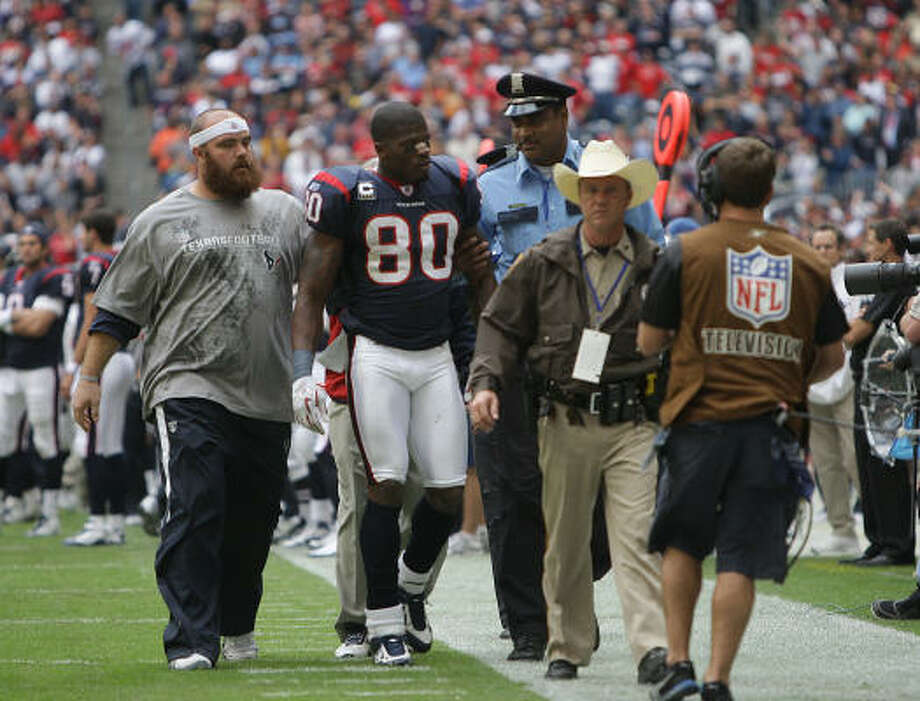 Injured teammate Kasey Studdard, left, helps escort Andre Johnson off the field after Sunday's confrontation with Cortland Finnegan. Photo: Karen Warren, Chronicle