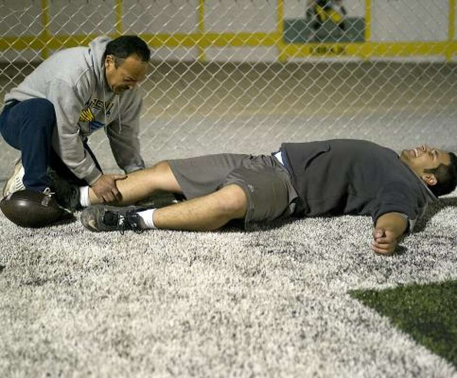 Coach Fernando Gallegos tends to a muscle cramp suffered by one of his players at a recent Friday night training session in Ciudad Juarez. Photo: Julian Cardona, Chronicle