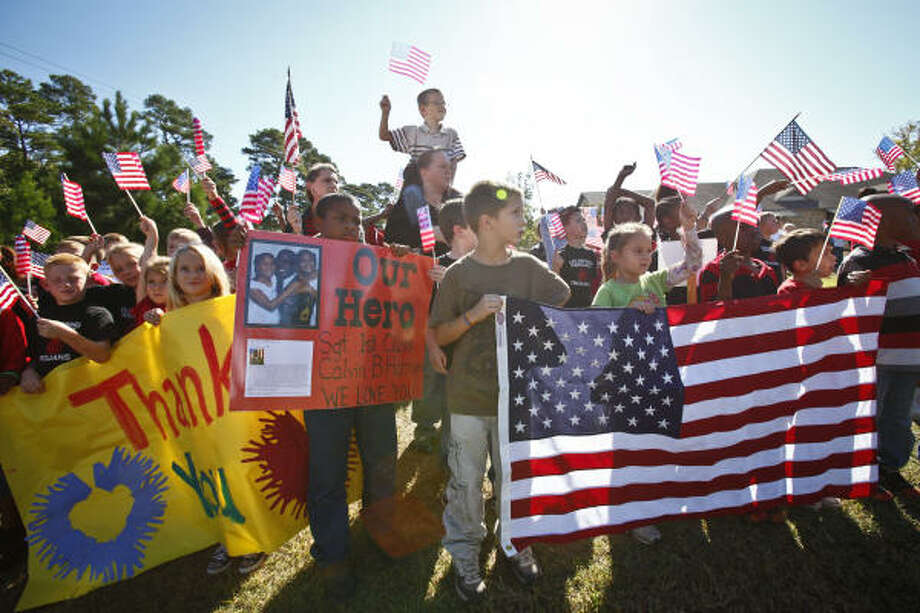 Elementary school students hold signs and flags Friday in honor of Sgt. 1st Class Calvin B. Harrison, who died in Afghanistan, as his funeral procession passes by in Coldspring. Photo: Michael Paulsen, Chronicle