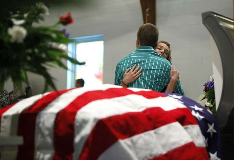 Travis McKinney is comforted by Cheyanne Graybeal next to the casket of McKinney's grandfather, mine victim Benny Ray Willingham, in Mullens, W.Va., on Friday. Photo: Carolyn Kaster, Associated Press