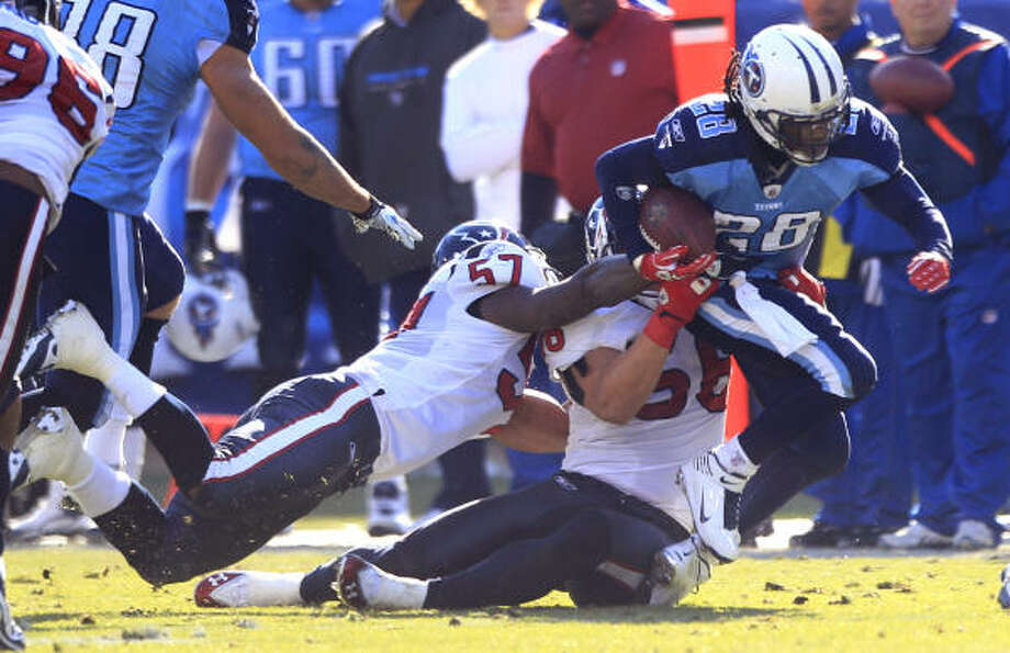 Titans running back Chris Johnson, right, tries to break free from the combined efforts of Texans linebackers Brian Cushing, center, and Kevin Bentley, left. Johnson shed enough tackles to gain 130 yards on 24 carries. Photo: Brett Coomer, Chronicle