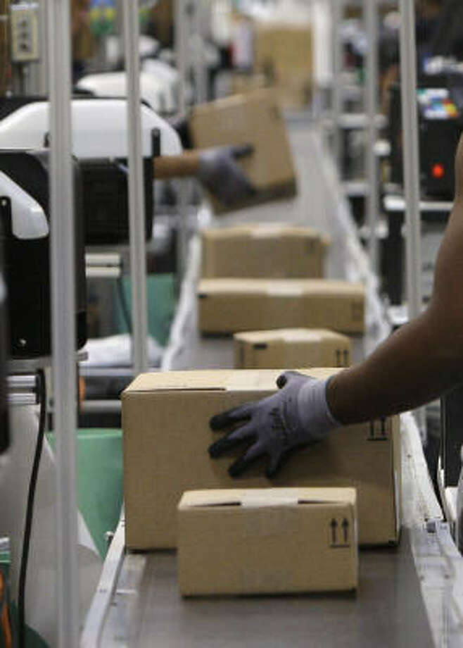 "Packed boxes head toward shipping trucks at an Amazon ""fulfillment center"" in Phoenix. Photo: Ross D. Franklin, AP"