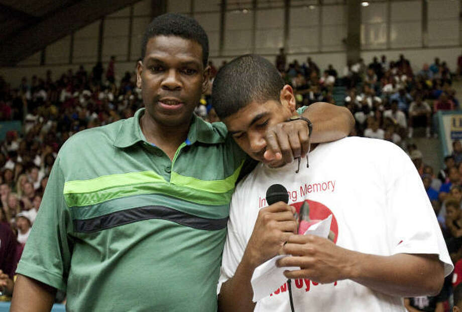 Bellaire's head basketball coach Bruce Glover, left, puts his arm around his player Jonathan Evans who breaks up as he makes a speech before a charity basketball game in memory of Tobi Oyedeji. Photo: Nick De La Torre, Chronicle