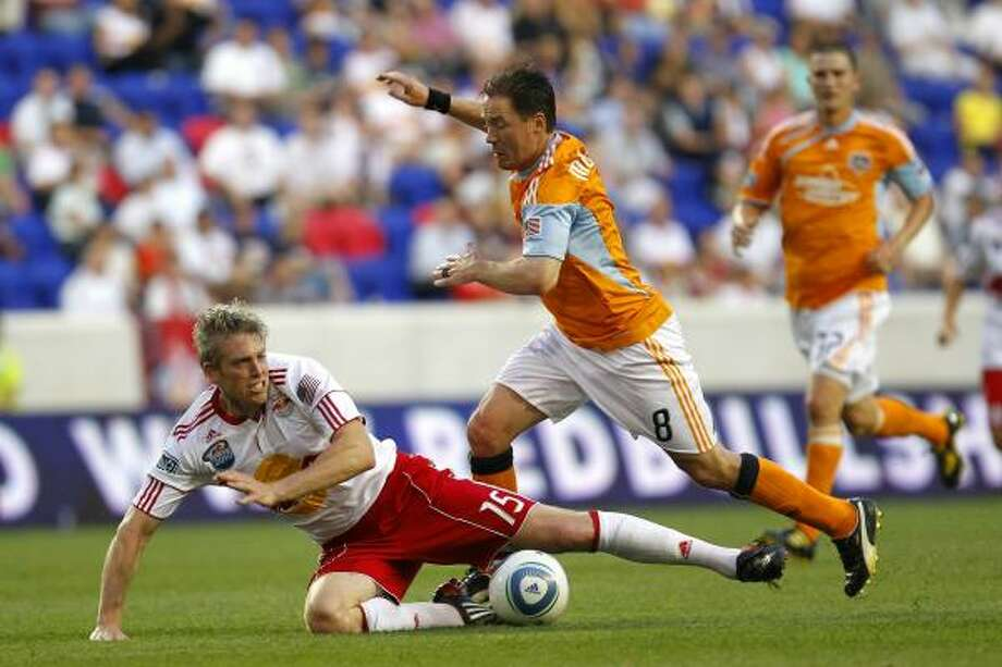 Dynamo defender Richard Mulrooney fouls Red Bulls forward John Wolyniec. Photo: Chris Trotman, Getty Images